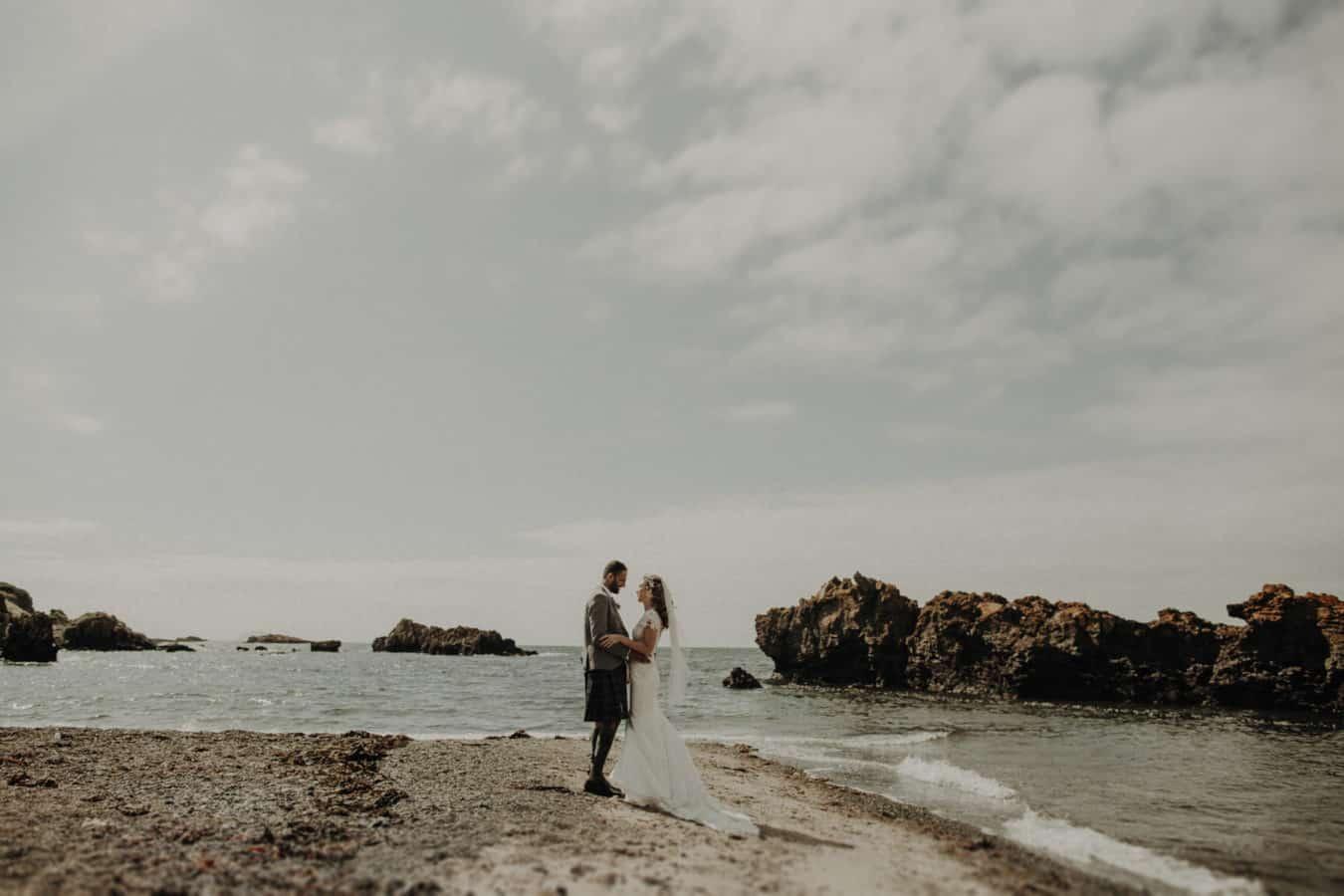 Bride and groom on teh beach with stones in Scotland Ayrshire Sunny daylena-sabala-scottish-glasgow-wedding-photographer-couple