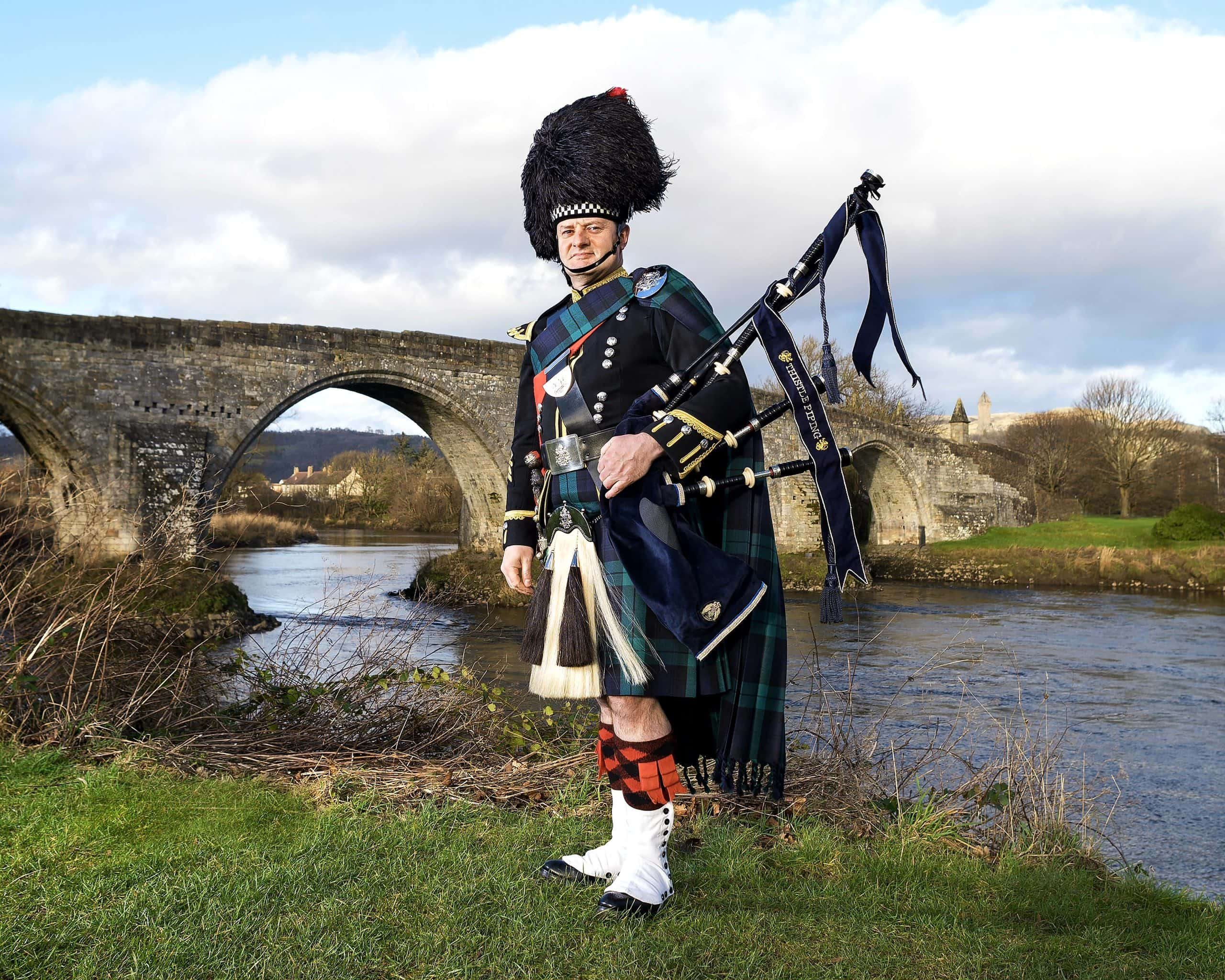 Wedding Piper Scotland in full regimental uniform with Stirling Bridge and Wallace Monument behind